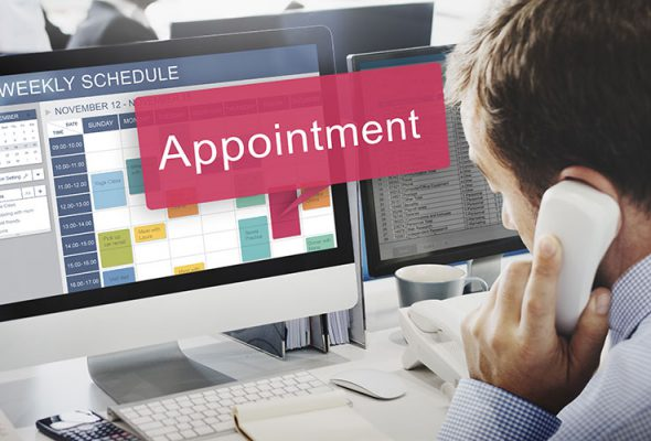 man on phone looking at computer displaying appointment calendar