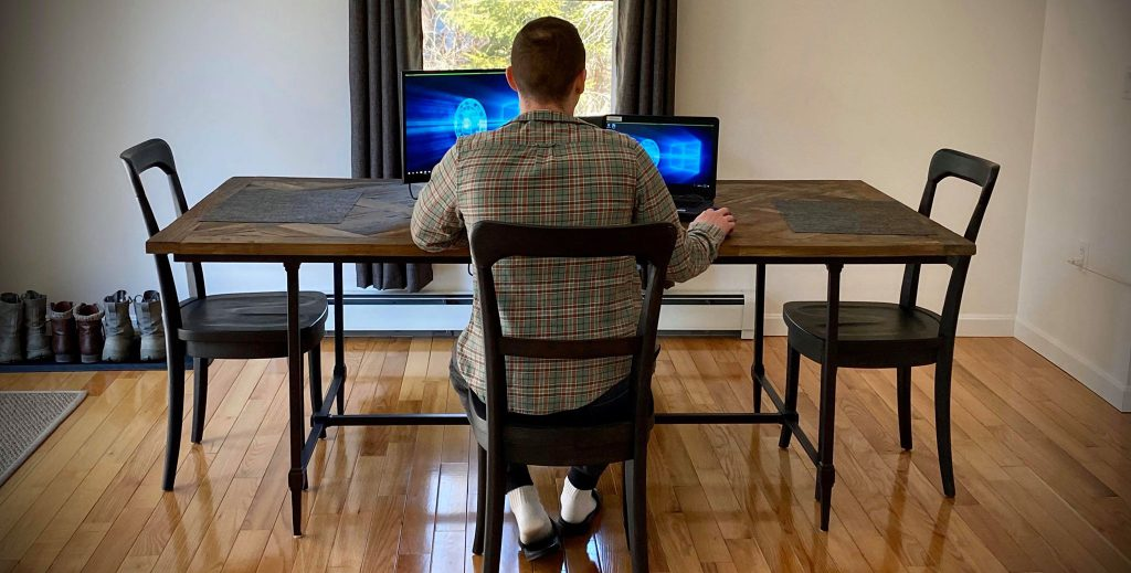 Back of man using computer while sitting at dining table